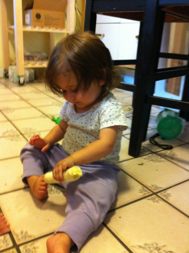 Lucy feeds a banana to her toes.