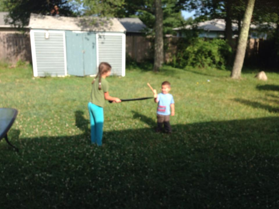 Bella and Anthony sword fighting.