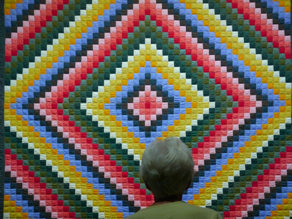 barnraising quilt with white haired lady