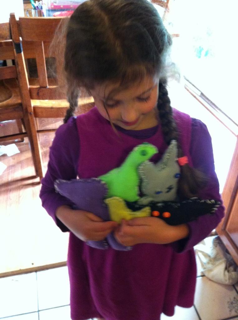 Sophie with her felt animal collection: beara, dinosaur, bird, bunny, batty.