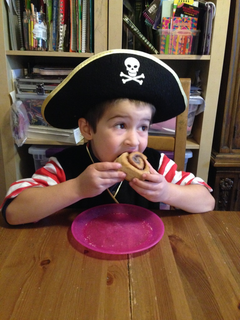 The pirate eats a cinnamon roll