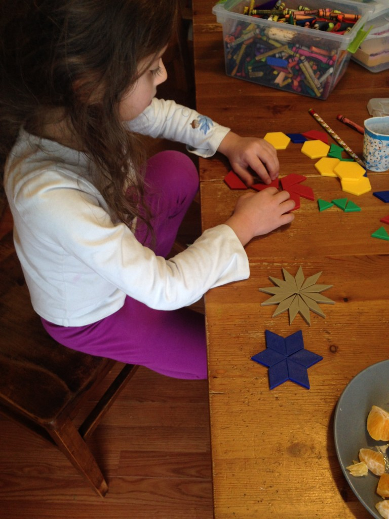 Sophie makes stars with pattern blocks, one for each season.
