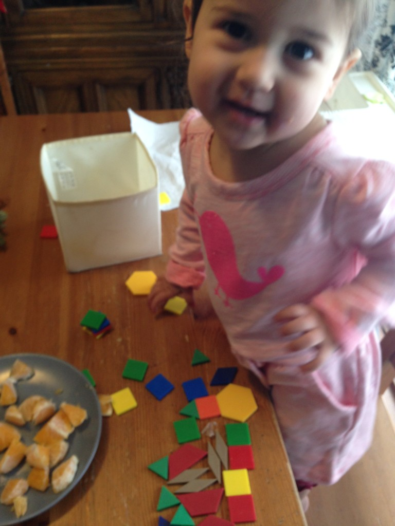 Lucy plays with pattern blocks.