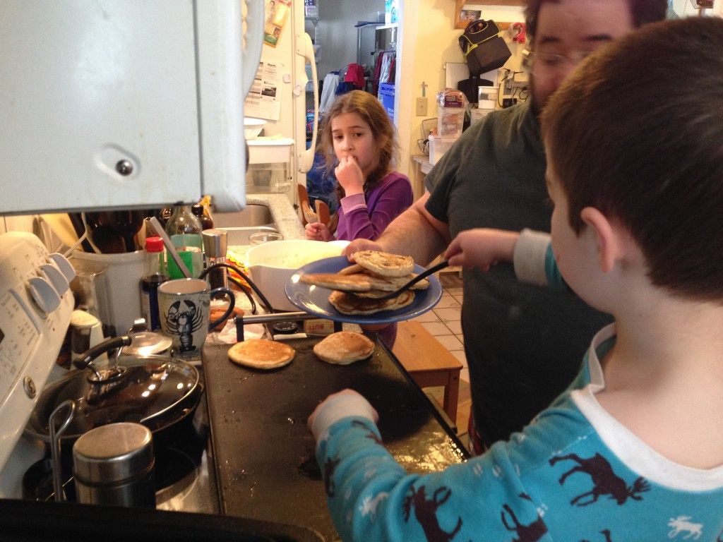 Ben flips the pancakes off the griddle.
