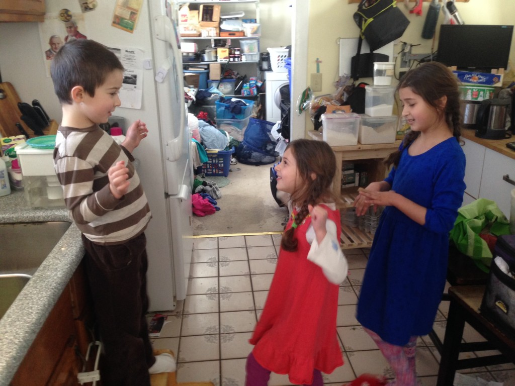 Ben, Sophie, and Bella take turns in an impromptu kitchen sing off. Ben is judging while his sisters sing. The winner will become the judge.