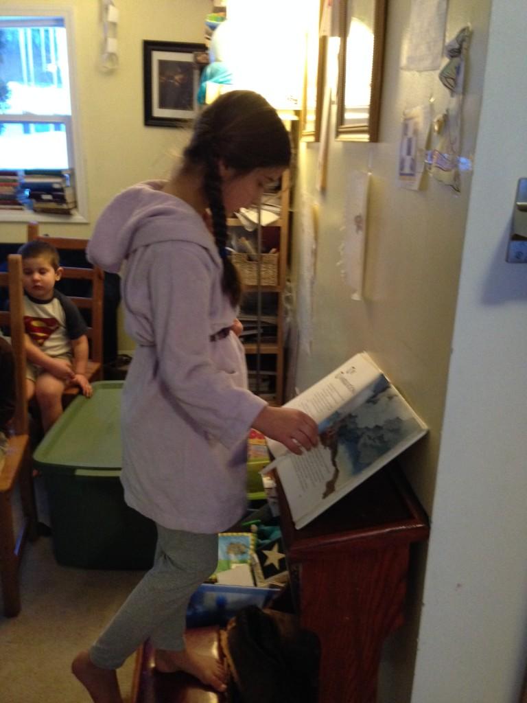 Bella plays priest, reading the Gospel