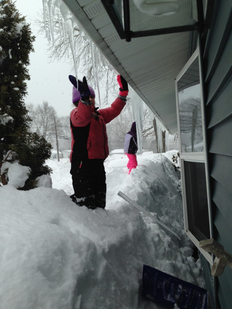Bella and Sophie help knock icicles off the eaves