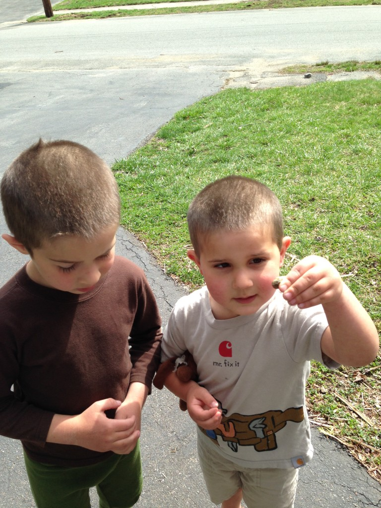 Anthony shows off the snail he found while Ben looks on.