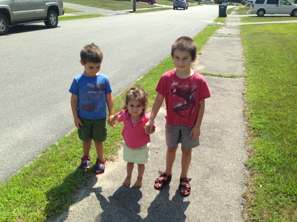 Big brother Ben takes Lucy and Anthony for a walk down the block.