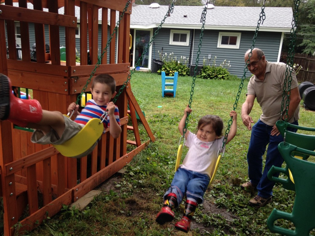 Grandad pushes Lucy on the swing.