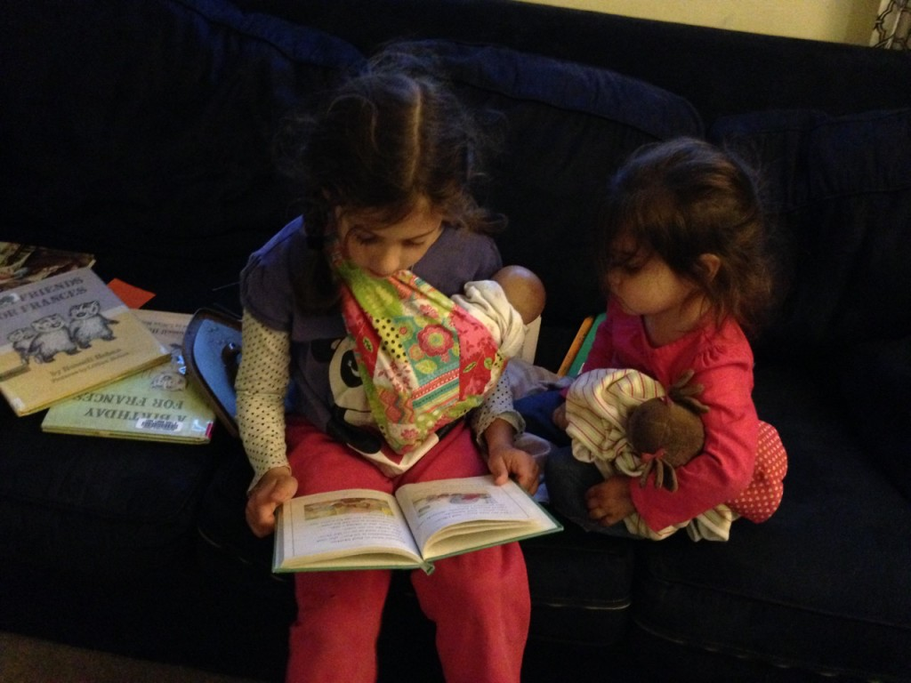 Sophie reads to Lucy while both cuddle dolls.