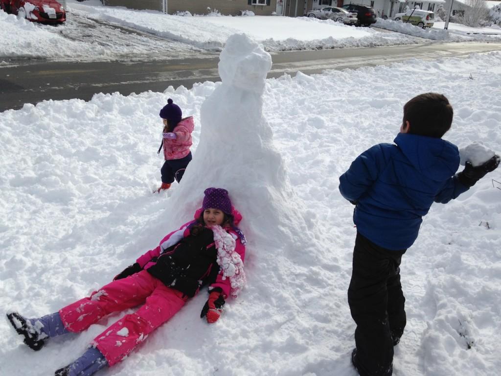Ben throws a snowball at the snowman.