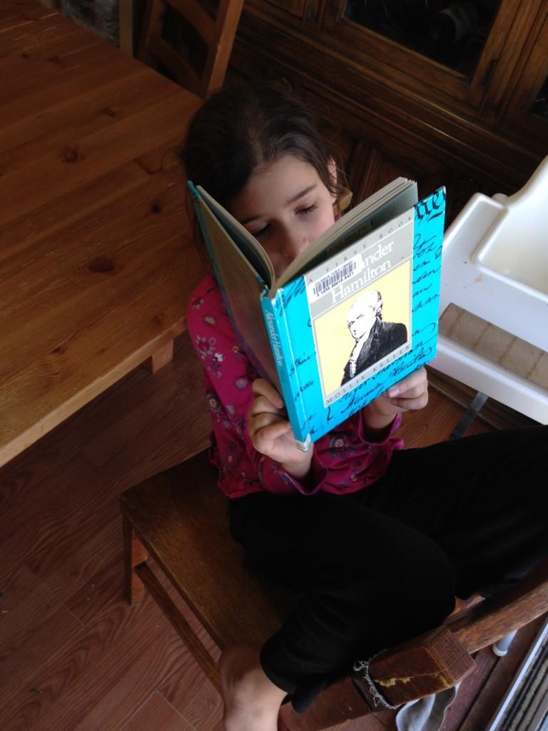 Bella reads about Alexander Hamilton.