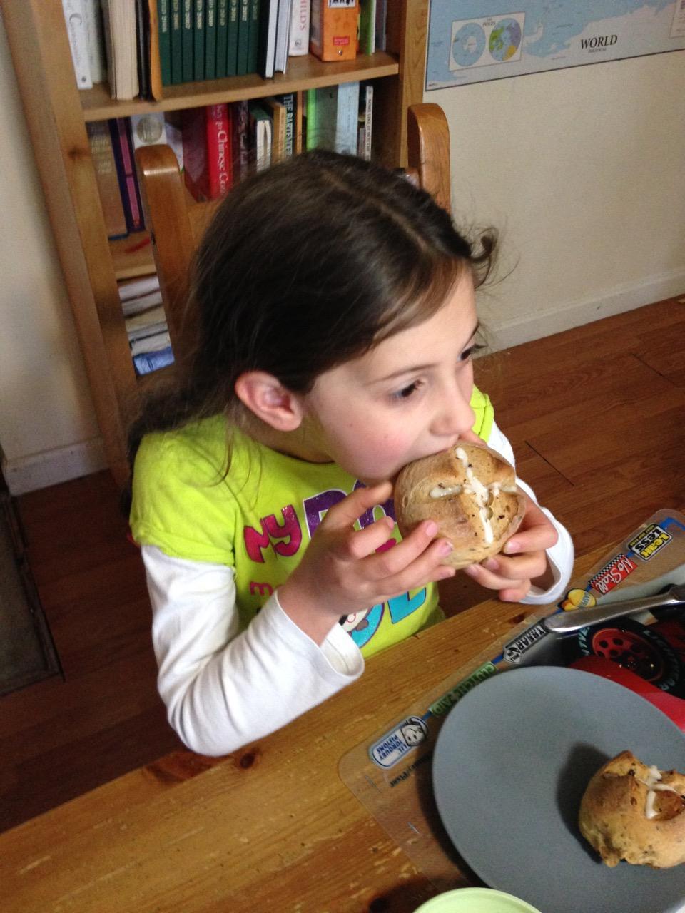 Sophie eats a hot cross bun.