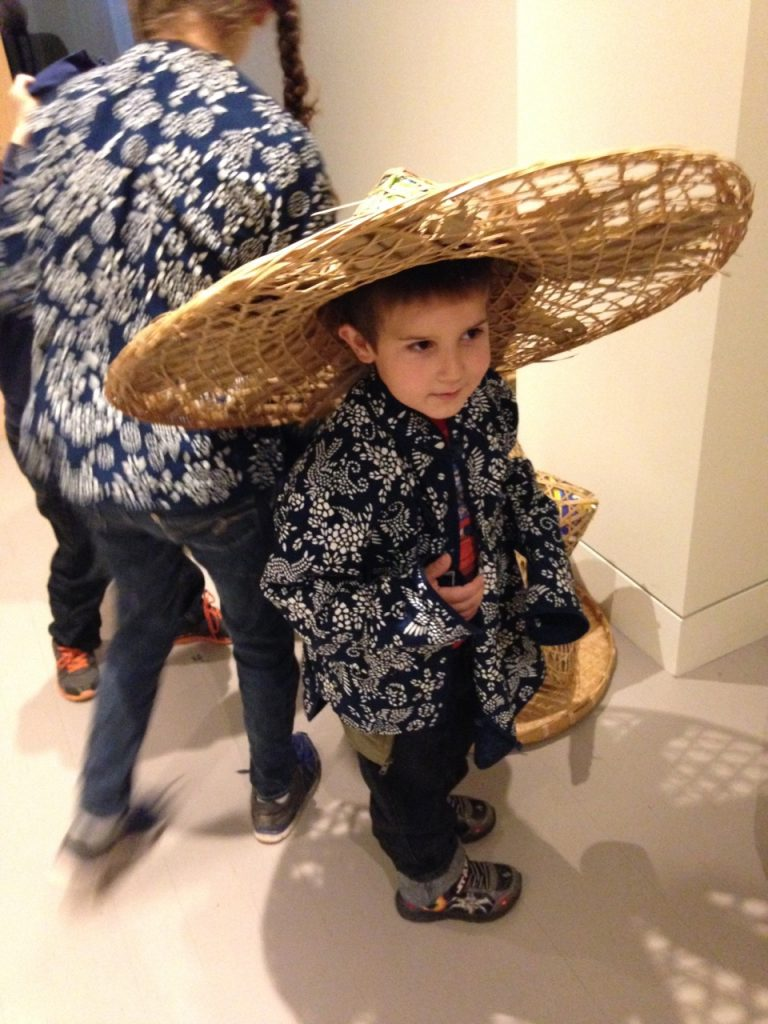 Anthony tries on a Chinese hat and jacket.