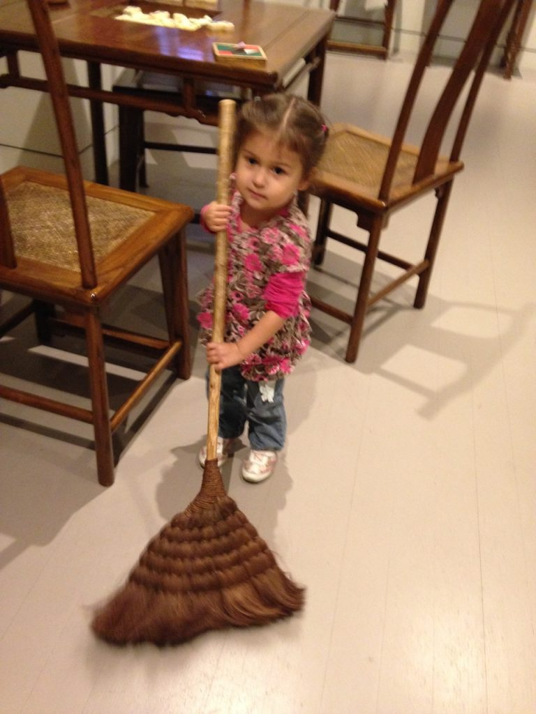 Lucy sweeps with a Chinese broom.