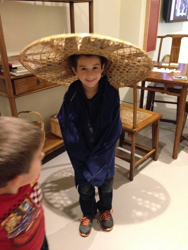 Ben tries on a Chinese hat and jacket.