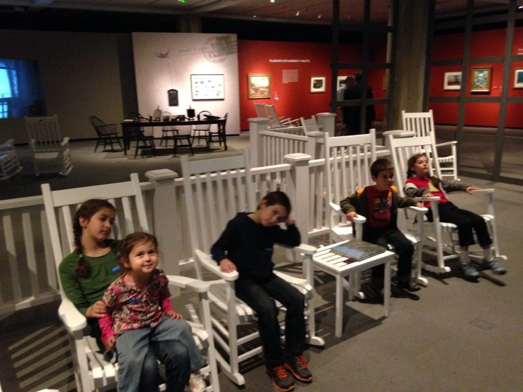 Rocking chairs looking at the sunset paintings.