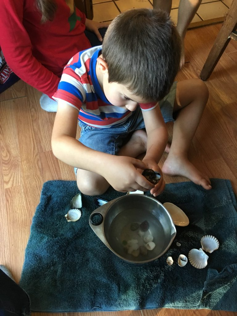 Anthony plays with shells and water.