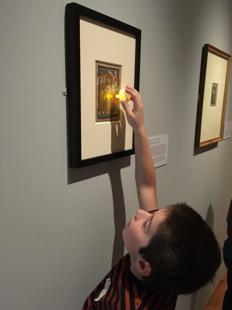 Ben holds his light up to the painting.